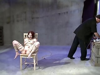 Slave with a gag in her mouth is tied to a chair while he tortures her